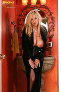 Rachel Aziani in black velvet coat, waist cincher and thigh high stockings; from Busty Rachel
